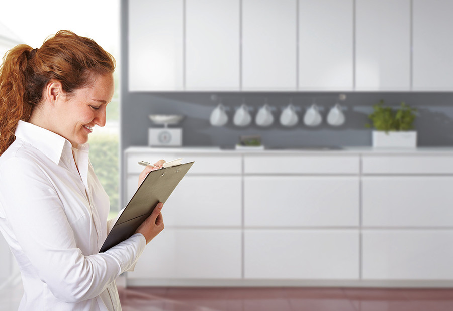 Woman in the kitchen with checklist for kitchen planning